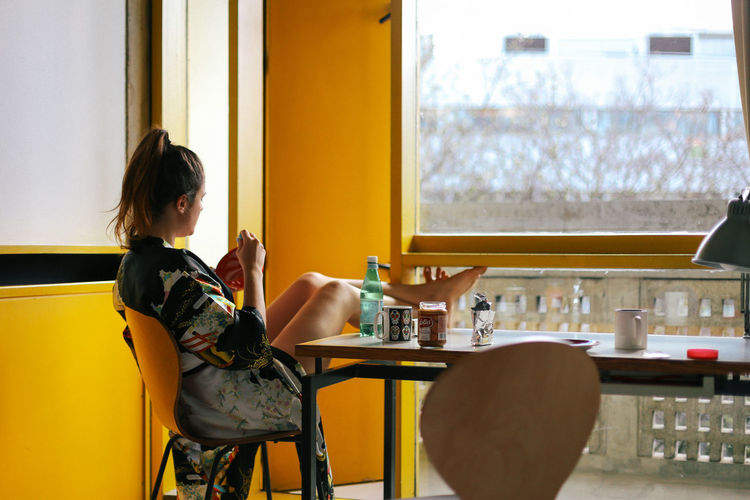 Side view of woman sitting in restaurant
