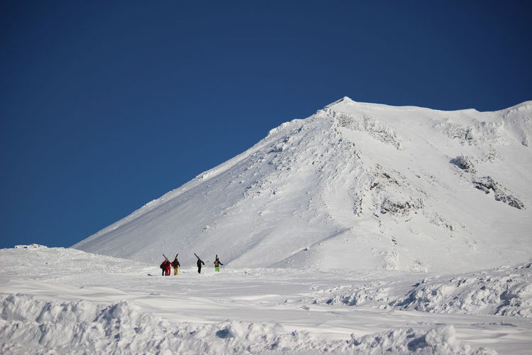 People on snowcapped mountain against clear blue sky