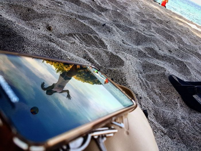 Reflection Of Woman On Screen Of Mobile Phone At Sandy Beach