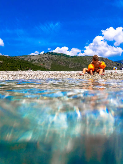 Water Surface Shot Of Boy Sitting At Beach During Sunny Day