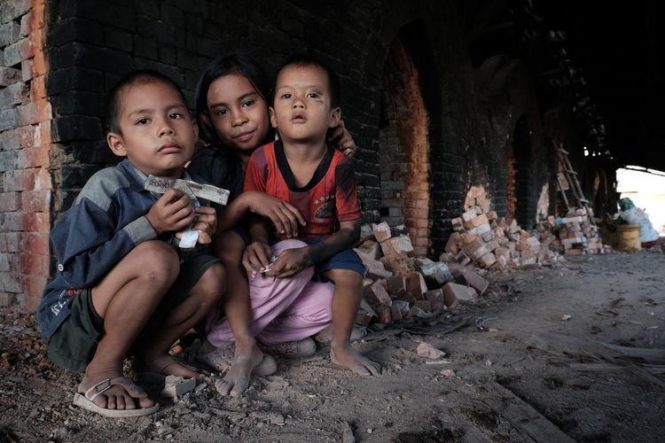 Portrait of siblings against brick wall