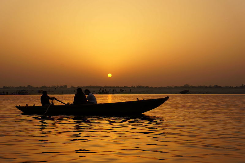 People on boat at ganges river against sky during sunset