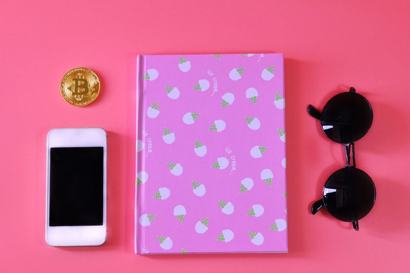 Directly Above Shot Of Pink Diary With Smart Phone And Sunglasses Over Colored Background
