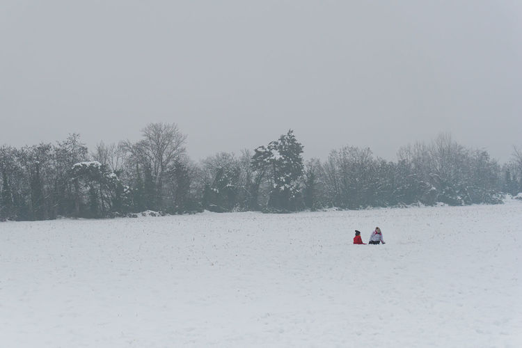 People on snow covered field against sky
