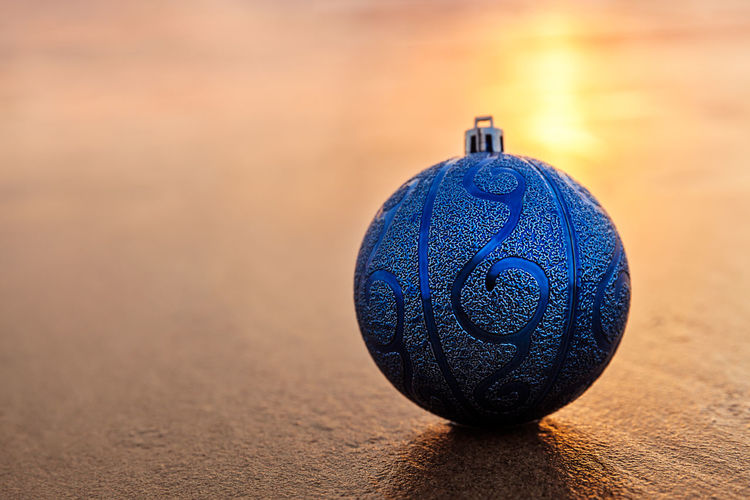Close-up of christmas ornament on sand at beach