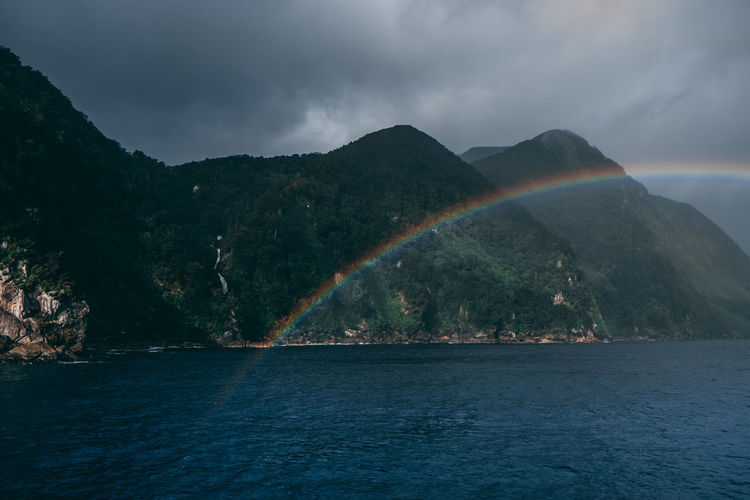 Scenic view of rainbow over sea and mountains