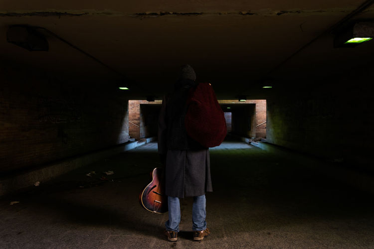 Rear view of man standing in underground walkway