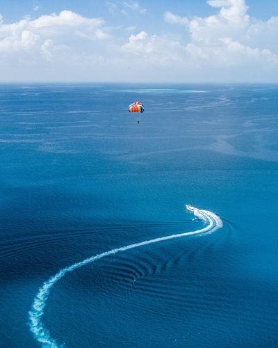 Parasailing Sea Water Blue Beauty In Nature Cloud - Sky Transportation Nature Day Land No People Tranquility Outdoors Nautical Vessel Beach Sky Scenics - Nature High Angle View Tranquil Scene Mode Of Transportation