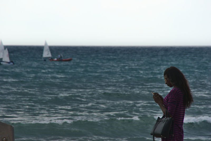 Side view of woman standing in sea against clear sky