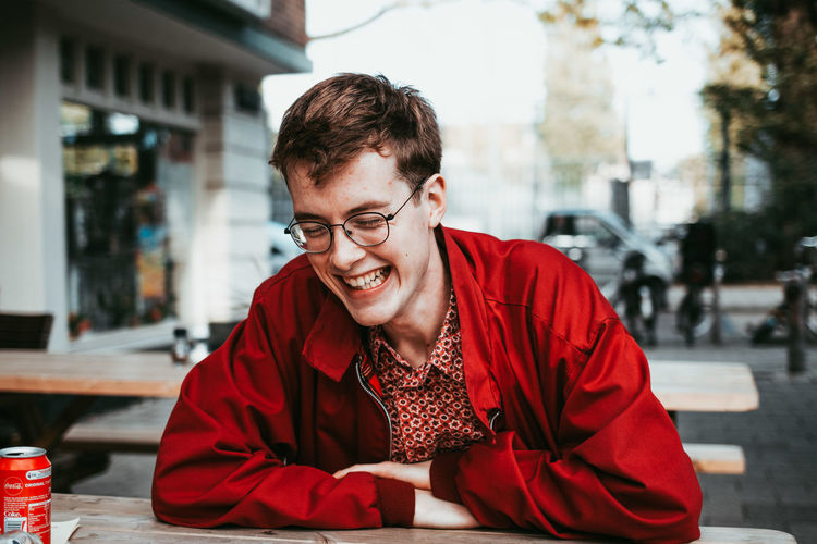 Casual Clothing Day Emotion Eyeglasses  Focus On Foreground Front View Glasses Hairstyle Happiness Lifestyles Looking At Camera One Person Outdoors Portrait Real People Red Sitting Smiling Table Waist Up Young Adult