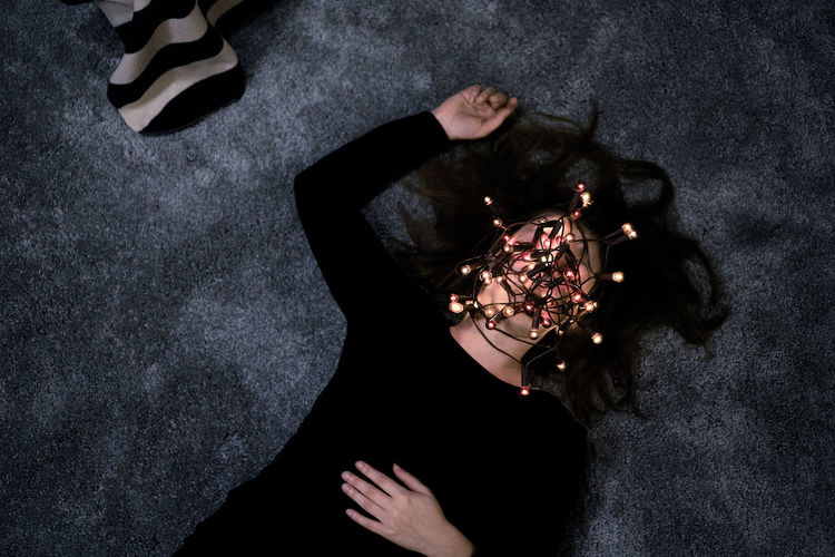 High Angle View Of Woman With Face Covered By String Lights