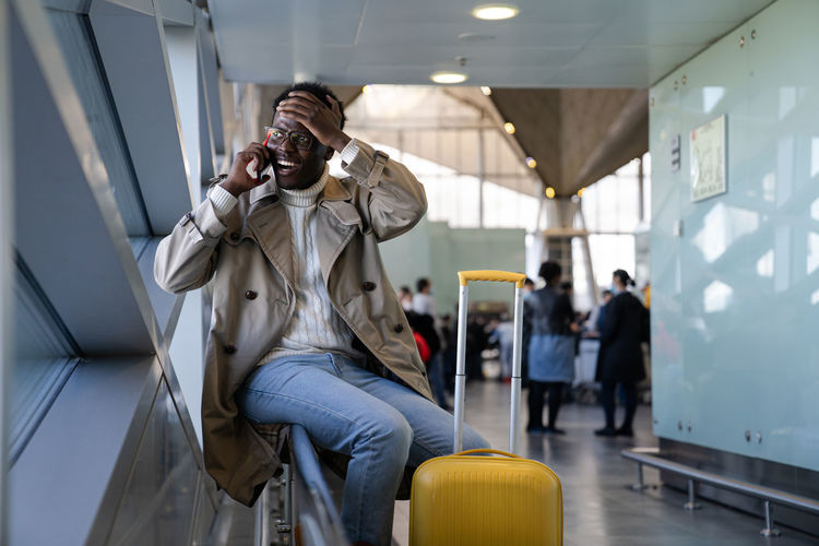 Black man shocked talking oncellphone sitting in airport, makes facepalm, forgot something important