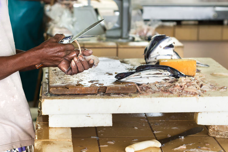 Midsection of man cleaning fish on table at market
