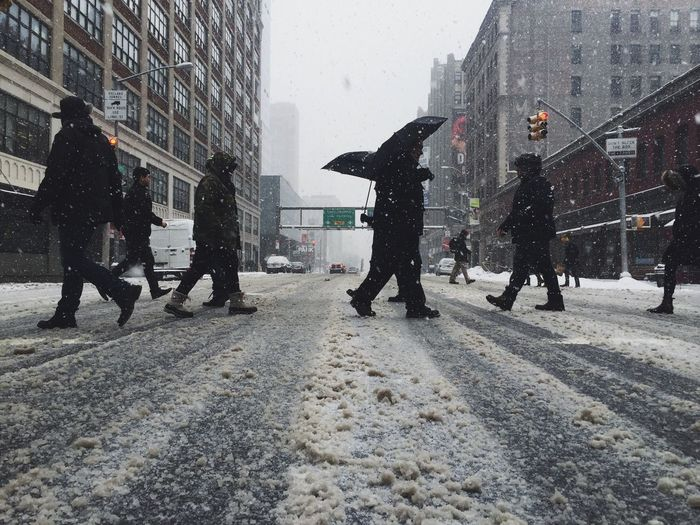 People walking on snowcapped street during snowfall in city