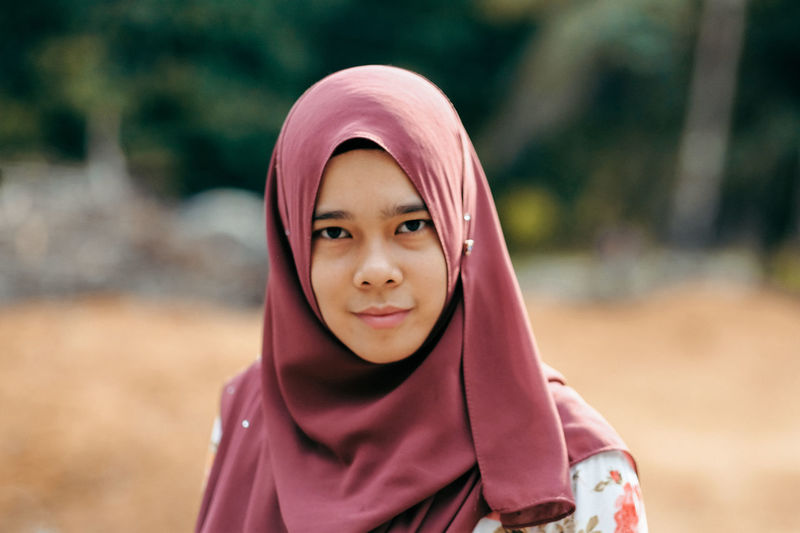 Close-up portrait of smiling young woman wearing hijab