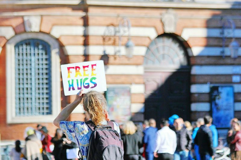 Man Holding Free Hugs Sign Against Building