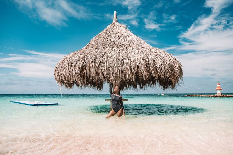 Woman standing at beach against blue sky