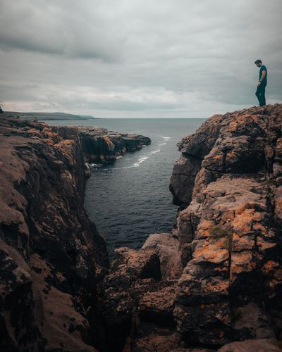 Man standing on rock formation by sea against sky