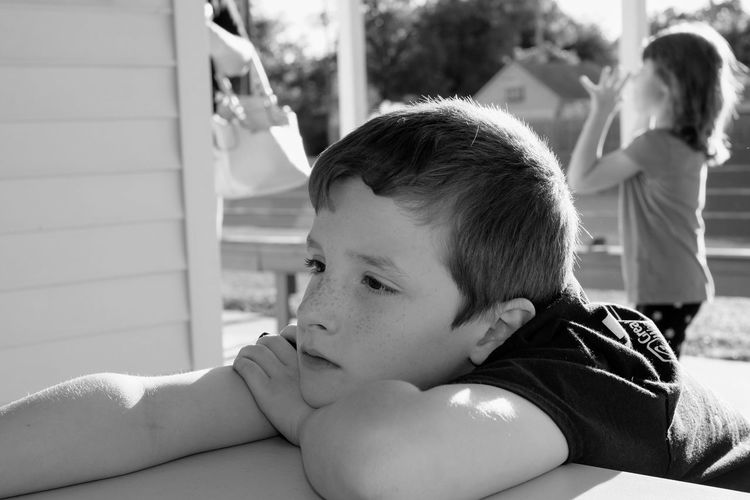 Close-up of thoughtful boy sitting outdoors