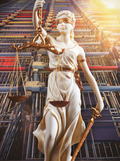 Low angle view of lady justice statue against shopping carts