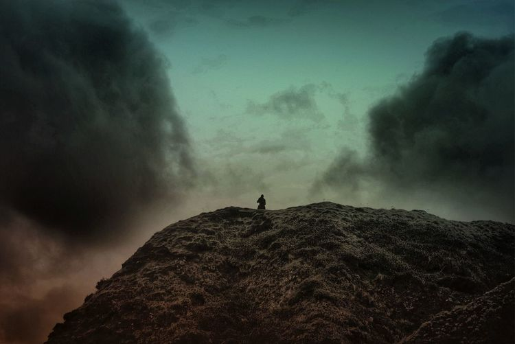 Silhouette person standing on landscape against sky
