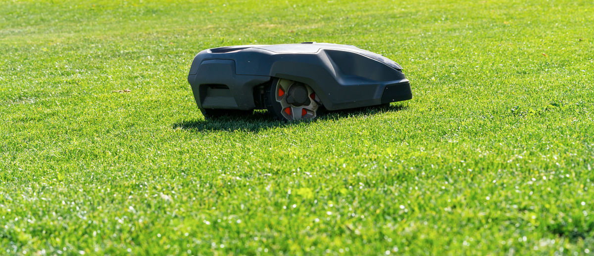 High Angle View Of Automatic Lawn Mower On Grass Field