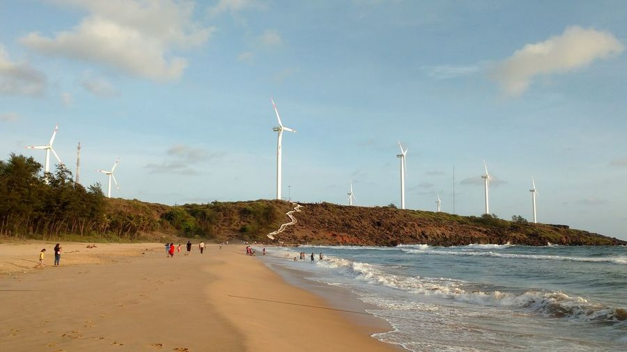 Beautiful Scene with Water , Sand , Trees , Windmills and Blue Sky on Devgad Beach
