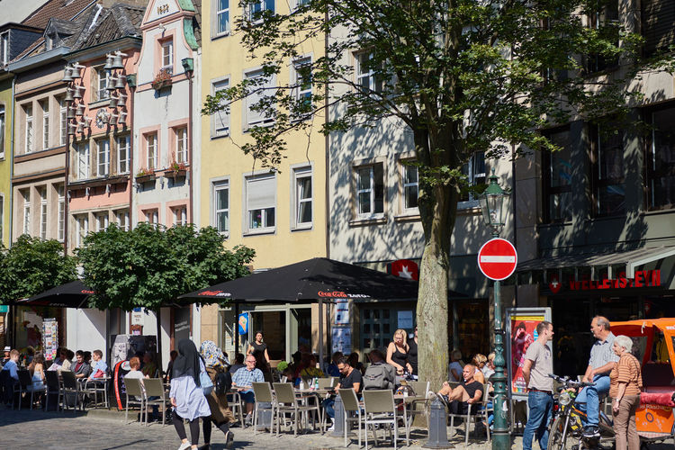 DUESSELDORF, GERMANY - AUGUST 17, 2016: People enjoy food and drinks at a historic Altstadt facade with the Glockenspiel Altstadt Atmosphere Bar Blu Sky City Life City Street Daytime Düsseldof High Resolution Lifestyles NRW Outdoors People R Relaxing Restaurant Rheinland-Pfalz  Rhine Promna S Shopping Tourism Travel Destinaton