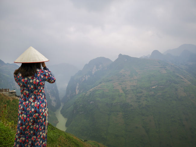 Young Vietnamese women facing and pose for camera with stunning view of the Nho Que river surrounded by mountains from the Ma Pi Leng pass in northern Vietnam Mountain Cloudy Green Color Meo Vac Vietnam Vietnamese Ao Dai Beauty In Nature Cloud - Sky Day Landscape Leisure Activity Lifestyles Looking At View Mountain Mountain Range Nature Non-urban Scene One Person Outdoors People Pose Real People Rear View Scenics - Nature Sky Sunrise Three Quarter Length Traditional Dress Tranquil Scene Tranquility Valley Women