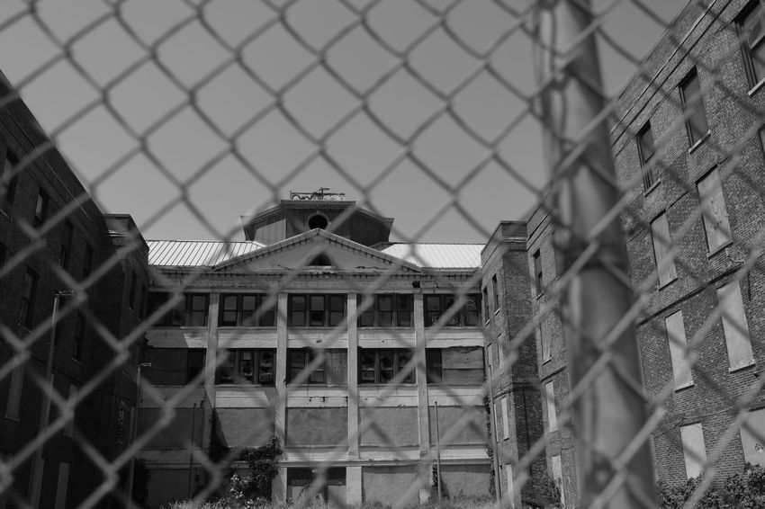 Riis Beach Abandoned Buildings Architecture Broken Windows Building Exterior Built Structure Chainlink Fence City Close-up Day Focus On Foreground Fujifilm_xseries FujifilmX_US Light And Shadow Metal No People Outdoors Pattern Photographyisthemuse Sky Through The Fence