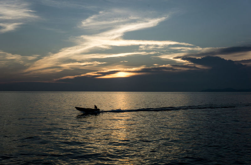 Silhouette man in sea against sky during sunset
