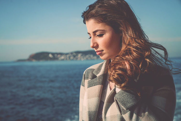 Close-Up Of Young Woman By Sea Against Sky