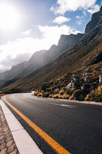 Asphalt Beauty In Nature Cloud - Sky Day Direction Dividing Line Empty Road Environment Marking Mountain Mountain Range Nature No People Outdoors Road Road Marking Scenics - Nature Sign Sky Symbol The Way Forward Transportation