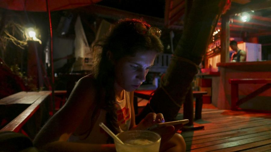 Young woman using mobile phone while sitting on chair at sidewalk cafe