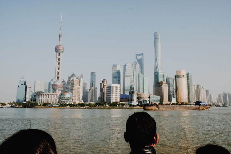 People Looking At City Skyline By River Against Clear Sky