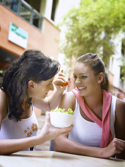 Smiling Woman Feeding Friend While Sitting At Restaurant