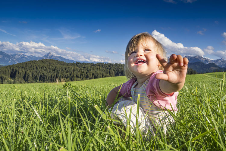 Smiling cute girl gesturing while sitting on grass against sky