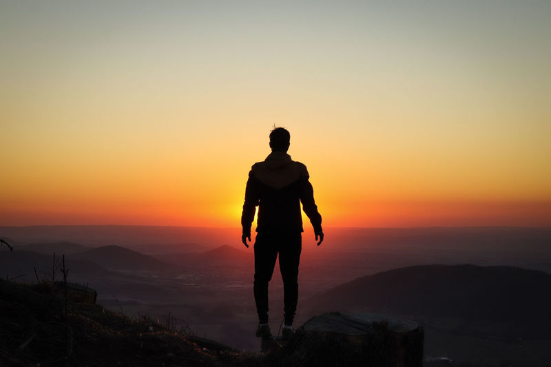 Rear view of silhouette man standing on mountain against orange sky