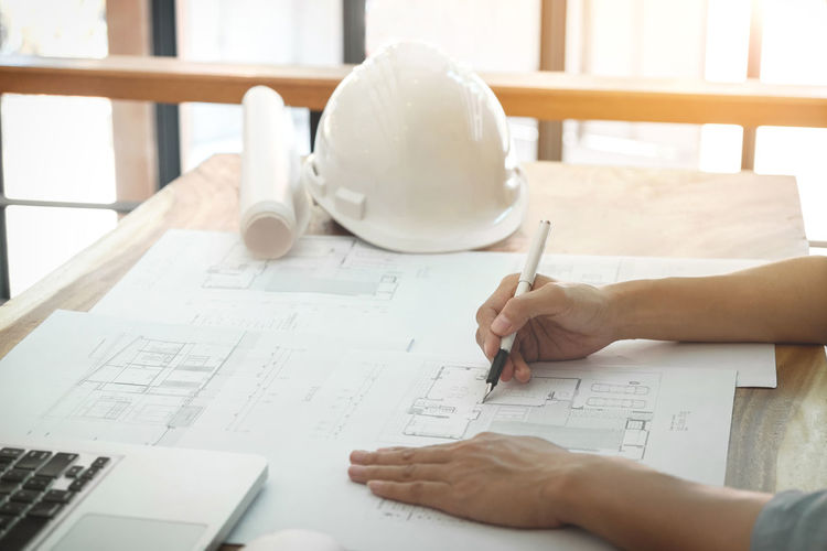 Cropped hands of male architect working at desk in office