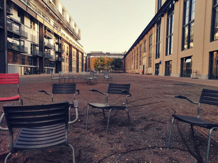 Empty chairs and table by buildings in city