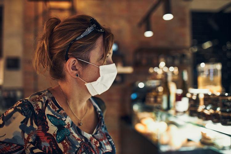 Woman wearing flu mask standing in cafe