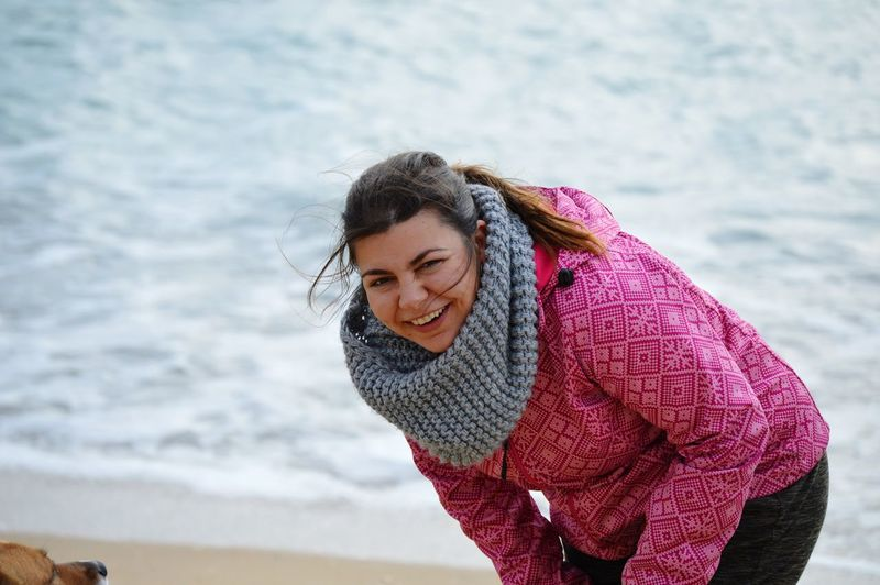 Portrait of smiling young woman wearing warm clothing while bending against sea at beach
