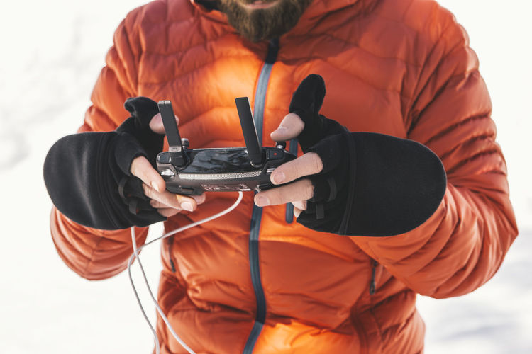 Man Using Remote Control While Standing On Snow Covered Field