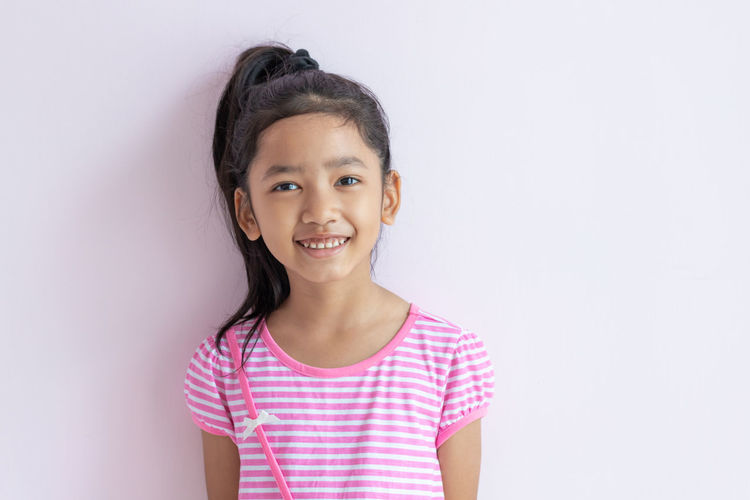 Portrait of a smiling girl standing against white background