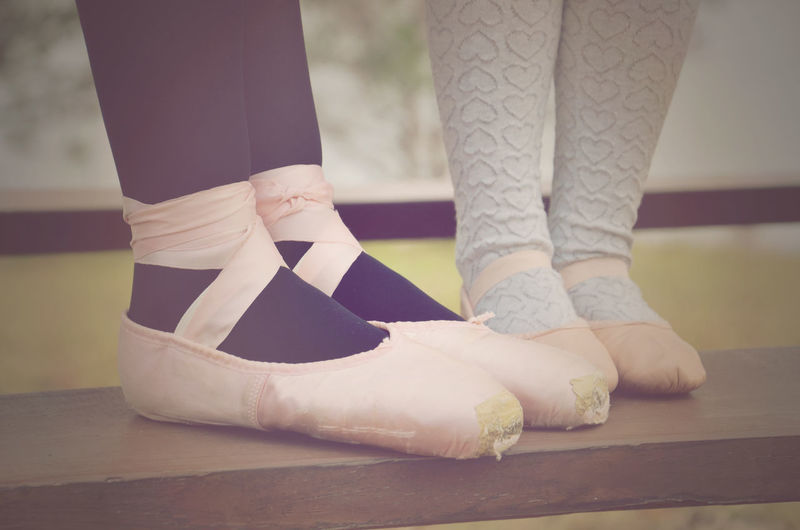 Low Section Of Woman And Girl Wearing Ballet Shoes