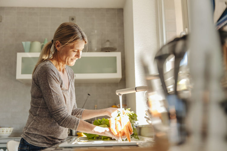Side view of woman standing at home