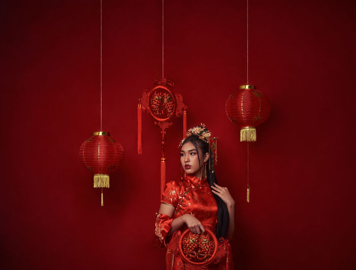 Woman holding lantern hanging against wall
