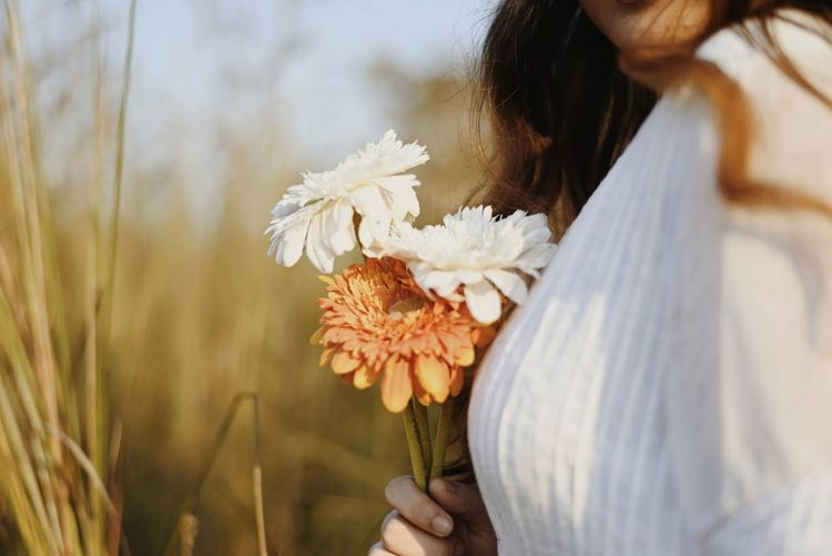 Close-up of woman holding white flowering plants