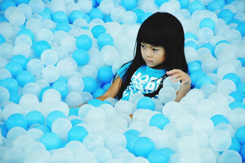 Cute Girl Looking Away While Sitting Amidst Blue And White Helium Balloons