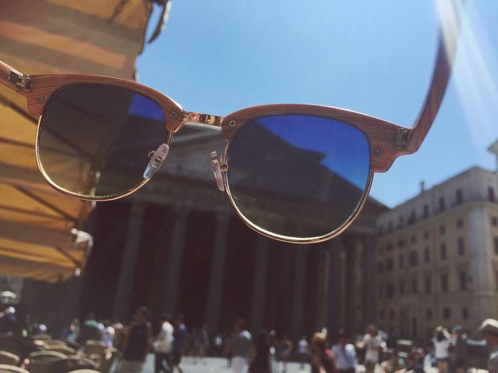 Sunglasses with blurred people against built structures
